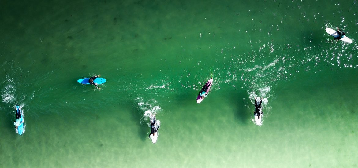 Surfers in clear green water